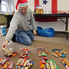 Allegra Boverman/Gloucester Daily Times. At the Office of Veterans Affairs in Gloucester on Wednesday, Steve Canning of Gloucester prepares eight piles of snacks and goodies to add to the care package boxes being prepared for eight soldiers serving in Afghanistan for the holidays.