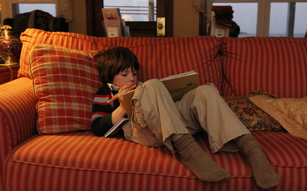 Allegra Boverman/Gloucester Daily Times. Making himself at home on a couch, Phin Kelly, 6, of Rockport, writes in his new journal while his mom, Sarah Kelly, an interior designer whose business is called The Roving Home, decorates an inn for the holidays in Rockport on Tuesday.