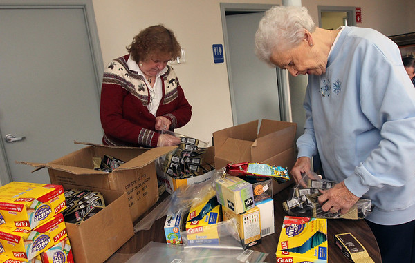Allegra Boverman/Gloucester Daily Times. From left are Trisha Rankin and Janet Silva, packing coffee and tea into bags as part of the care packages they were putting together on Wednesday at the Office of Veterans Services  to send to eight soldiers serving in Afghanistan.