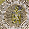 """Allegra Boverman/Gloucester Daily Times. Bruce Ware, who recently moved to Gloucester, is displaying some of his intricate beadwork at Sawyer Free Library. This is a work he made as a holiday gift for a friend, with the """"om"""" symbol."""