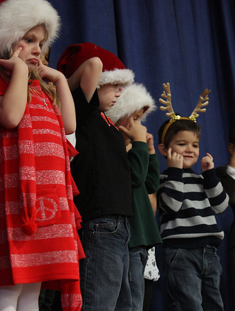 MARIA UMINSKI/GLOUCESTER DAILY TIMES Kindergarteners (L to R) Maggie Reynolds, Aiden Phillips, Kyle Collins and Ethan Tschida act out parts of their holiday song during the Veterans Memorial Elementary School Holiday Sing-a-Long on Thursday.