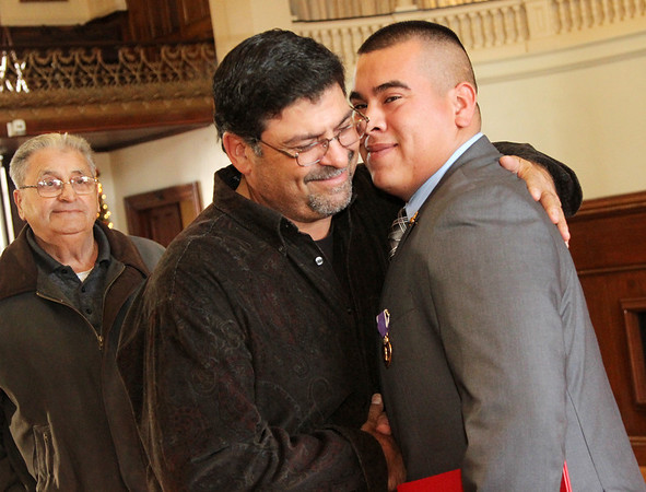 Allegra Boverman/Gloucester Daily Times. Adam Curcuru, right, of Gloucester received a Purple Heart medal on Friday for his injury during his service as a lead gunner in the Third Battalion Sixth Marines in Afghanistan. He is hugged by his father, Joe Curcuru III and behind him is his own father and Adam's grandfather, Joe Curcuru, all of Gloucester, after the ceremony.