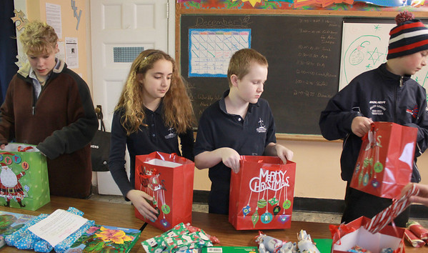 Jim Vaiknoras/Gloucester Times: East Gloucester Day School students in Matthew Racine's class. Laney Lavelle, Anabelle Palumbo, Danny McShea, and Mark Turner fill gift bags with various necessities, such as soap, shampoo, and toothpast for the homeless shelter in Gloucester. 36 packages are being put together for 36 people at Action. Each student did chores to raise money for a $10 gift card to be put in each bag.