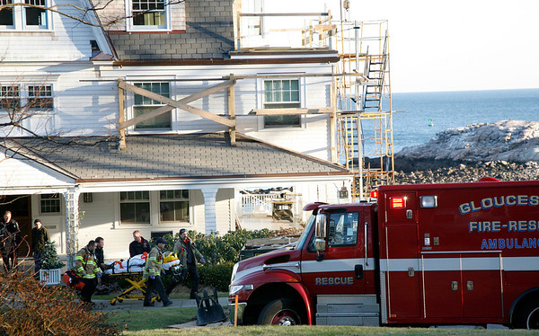 Allegra Boverman/Gloucester Daily Times. Gloucester firefighters prepare to take a man  to the hospital after he reportedly fell off a roof at this home at 104R Hesperus Avenue in Magnolia on Friday afternoon.