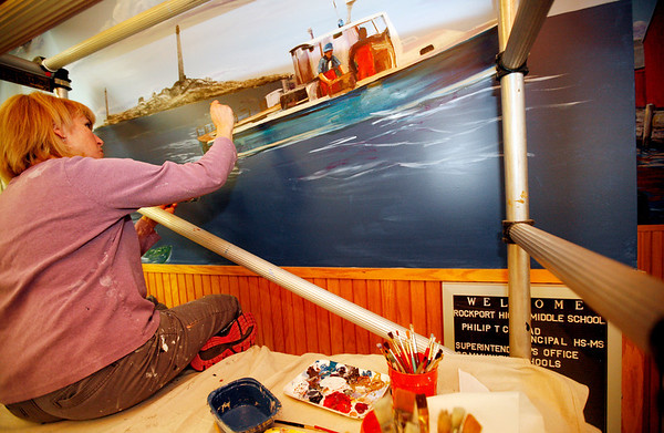 Allegra Boverman/Gloucester Daily Times. Tina Lamond, who works at Rockport Elementary School, has been working on a mural in the main lobby at Rockport High School depicting the school's mascot and local scenery. She usually paints after school and at night when there is less traffic in the hallway.