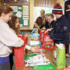 Jim Vaiknoras/Gloucester Times: East Gloucester Day School students in Matthew Racine's class.Lainy Turner, Sophie Palumbo,  Laney Lavelle, Anabelle Palumbo, Danny McShea,Mark Turner, and Sedona Gillard fill gift bags with various necessities, such as soap, shampoo, and toothpast for the homeless shelter in Gloucester. 36 packages are being put together for 36 people at Action. Each student did chores to raise money for a $10 gift card to be put in each bag.