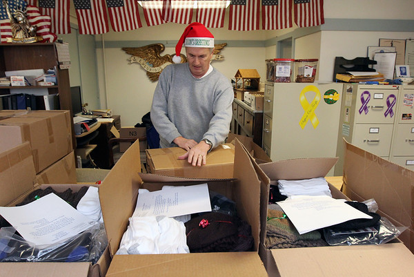 Allegra Boverman/Gloucester Daily Times. Steve Canning of Gloucester seals boxes of warm clothing, scarves, socks, blankets, helmet liners and more for eight soldiers serving in Afghanistan from the area at the Office of Veterans Services on Wednesday morning. The blankets were donated by Essex County Sheriff Frank Cousins.