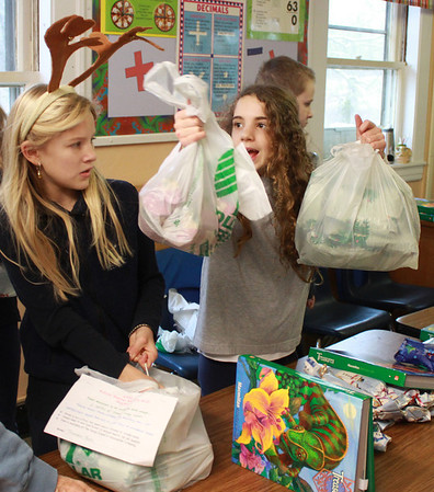 Jim Vaiknoras/Gloucester Times: East Gloucester Day School students in Matthew Racine's class. Sophie Palumbo, and Sedona Gillard fill gift bags with various necessities, such as soap, shampoo, and toothpast for the homeless shelter in Gloucester. 36 packages are being put together for 36 people at Action. Each student did chores to raise money for a $10 gift card to be put in each bag.