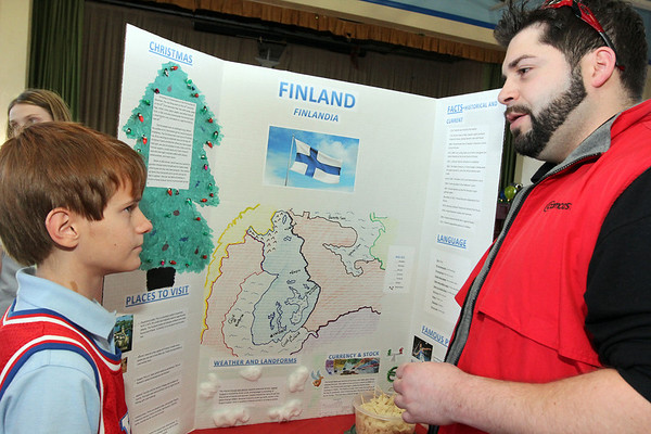 Allegra Boverman/Gloucester Daily Times. St. Ann Middle School sixth grader Michael Williams talks about Finland, where his grandfather is from, to visitor Tom Scola, during the Heritage Fair on Tuesday. The middle school students have spent time studying countries where they have ancestors and family or are from themselves, and put on display information about their cultures, customs, made food native to those countries and discussed how Christmas is celebrated in those countries. The students and teachers also created a cookbook with 40 recipes from around the world and proceeds from the cookbook sales will fund middle school activites for next year.