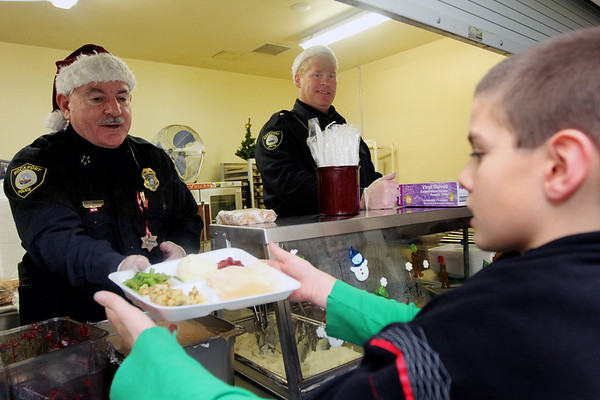 """Allegra Boverman/Gloucester Daily Times. The Rockport Police Department served lunch to Rockport Elementary School students on Thursday, the second year they have done so. Leftovers from the lunch, which included turkey, stuffing, mashed potatoes, gravy, cranberry sauce, string beans and rolls, were brought to the Action homeless shelter in Gloucester immediately following. Chief John """"Tom"""" McCarthy and Lt. Mark Schmink serve Austin Matus, a fourth grader."""