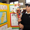 Allegra Boverman/Gloucester Daily Times. Talking about Portugal, St. Ann Middle School eighth grader Gabriela Llanos shows off a brinquinho, a musical instrument that sets the rhythm for dances in Portugal, while also wearing a bone, a hat her grandfather bought for her there, during the Heritage Fair on Tuesday. <br /> The middle school students have spent time studying countries where they have ancestors and family or are from themselves, and put on display information about their cultures, customs, made food native to those countries and discussed how Christmas is celebrated in those countries. The students and teachers also created a cookbook with 40 recipes from around the world and proceeds from the cookbook sales will fund middle school activites for next year.
