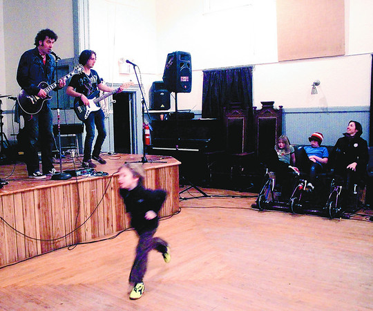 JIm Vaiknoras/Gloucester Times: Matthew Swift is a blur as he dances to teh sounds of the rock band Melodeego. at Spiran Hall during New Years Rockport Eve. The bands show is completely powered by people peddling on the right.