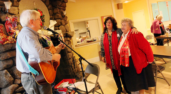 Allegra Boverman/Gloucester Daily Times. The Grace Center, Inc. held a celebration of its first year on Wednesday. From left, Keith Allen of Newburyport performed, and volunteers Anita Pandolfe Ruchman and Arlene Durkee sang along. On the mantle are stockings filled with necessities for each guests.