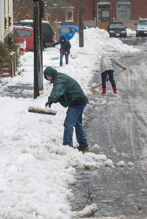 Desi Smith Staff photo/Gloucester Daily Times. Steve Connors shovels out in front of his home on Mason Street as well as his neighbors Amy Knoseworth and Liz Blatchford after Saturday nights storm. December 15,2017