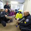 Desi Smith Staff photo/Gloucester Daily Times. Officer Rob Gilardi (left) and Sgt. Paul Francis places a baseball type card of themselves into a Essex police binders of Anya Bixby 7, and her brother Wesley 5, of Essex Thursday afternoon as Chief Peter Silva looks on. Chief Silva had an idea to have the cards made up of all his departments officers as an effort to get the kids and the public to know and trust their police. Also the first to fill the binder with all the departments officers, will get a new bike. December 12,2013