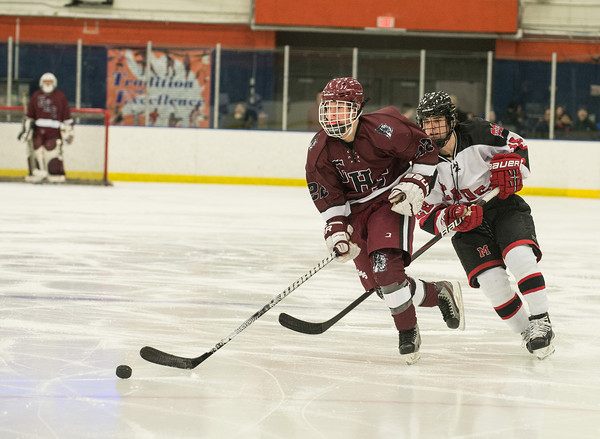 Desi Smith Staff photo/Gloucester Daily Times. Gloucester's Liam Lyons moves the puck up ice followed closly by Marbleheads Owen Piccariello Saturday afternoon in the season opener at Salem State University Rockett Arena in Salem.   December 14,2013