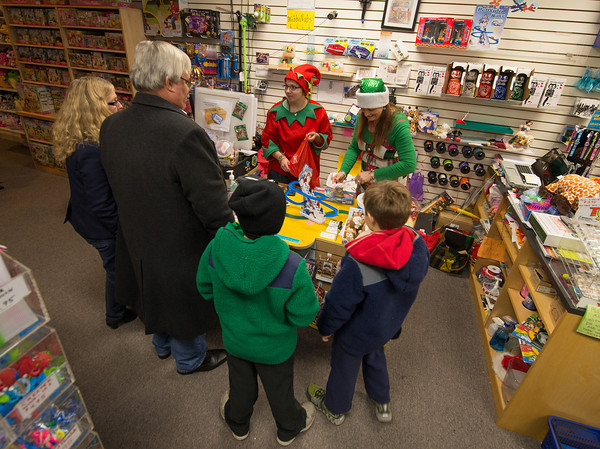 Desi Smith Staff photo/Gloucester Daily Times.  Ginger and George McKechnie (left) of Gloucester stopped by Toodeloos for some christmas gifts as Ali Goolsby (left) and ownwer Lisa Fornero wrap the gifts, while two boys watch an electric toy display on the counter Thursday night during Family and Friends Night. Stores stayed open late with most offering discounts or specials. December 12,2013