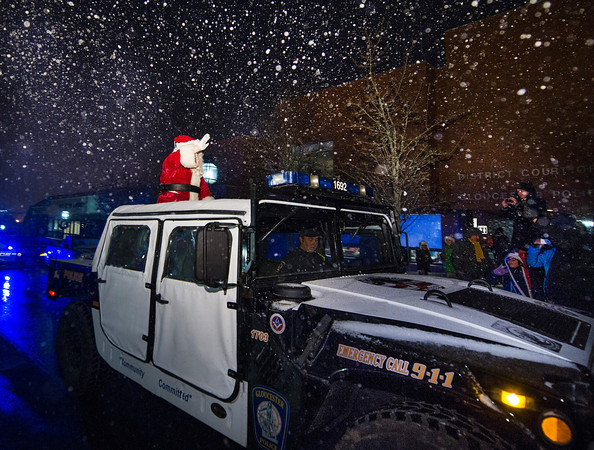 Desi Smith Staff photo/Gloucester Daily Times. Santa waves to the crowd as he arrives by Police Hummer on a snowy Saturday night, at the annual lighting in front of the Gloucester Police Station on Main Street.
