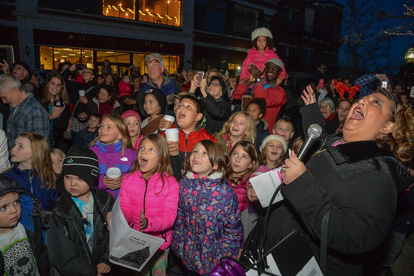 Desi Smith/Staff Photo.   Mayor Sefatia Romeo Theken leads a group of children and the crowd, in the final count down at the annual lobster trap tree lighting held Saturday night on Main Street.  December 12,2015.