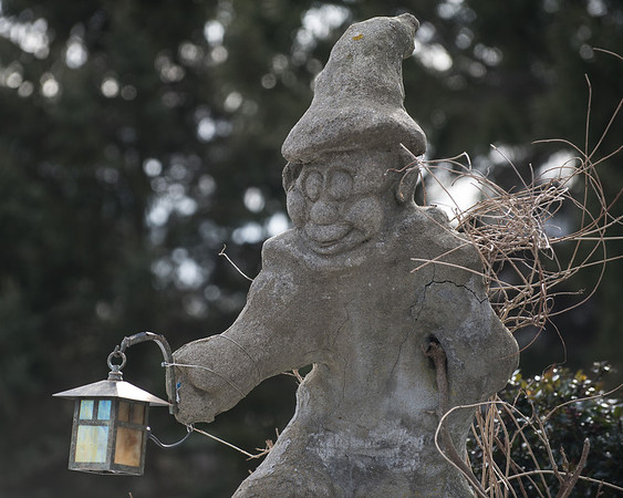 Desi Smith Staff photo/Gloucester Daily Times.    A stone elf like figure with a lamp helps light the way when night falls at a home on Spring Street in Essex Friday afternoon.   January 31,2013.