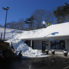GAIL McCarthy/Staff photo 2/16/15<br /> Snow at The Commons, a new shopping area in Gloucester, is cleared from the roof where it connects with the snow pile below.