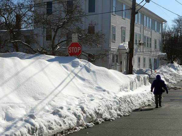 GAIL MCCARTHY/Staff photo <br /> <br /> Artist Pamela Fox walks alongside the snow banks on School Street in Rockport.