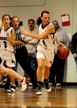 Manchester : Manchester's Lizzy Ball fakes out a defender with a behind the back dribble, while bringing the ball up court, last night at M/E High School. Photo by Desi Smith/Gloucester Daily Times Wednesday February 25, 2009.