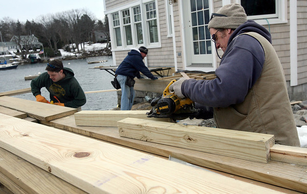Gloucester: From left: Micah Nimon, Jerry McKay and Arty Gobeil build a deck for a home on River Road overlooking the Annisquam River yesterday afternoon. The crew needed to build a support structure first because the deck is directly over the water. Photo by Kate Glass/Gloucester Daily Times Tuesday, February 10, 2009
