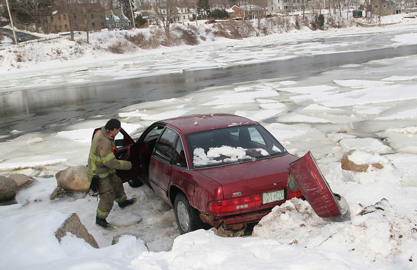 Gloucester: Gloucester firefighter John Nicastro investigates a car that lost control and almost ended up in the Mill RIver behind the Richdale parking lot off Washington Street Saturday monring. Mary Muckenhoupt/Gloucester Daily Times