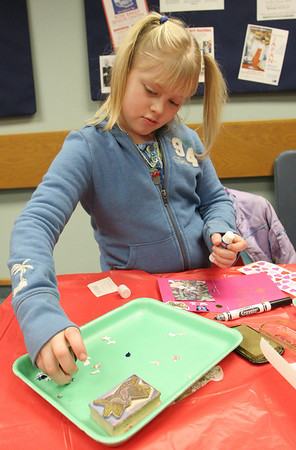 Gloucester: Allie Sears, 8, of Gloucester works on a Valentine's Day card for her big sister at the Sawyer Free Library Saturday afternoon.  Children came to the library to make card with Jesse Brown who provided special paper, stickers, ribbons, and stamps to make unique Valentine cards. Mary Muckenhoupt/Gloucester Daily Times