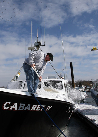 Gloucester: Mike Goodwin cleans snow off Peter Libro's boat, Cabaret IV, at the Jodrey State Fish Pier yesterday while Libro vacations in St. Lucia. Goodwin says they won't be fishing for a while due to the regulations. Photo by Kate Glass/Gloucester Daily Times Wednesday, February 4, 2009