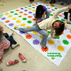 Gloucester: Madolin Beaulieu, 7, left, watches as her twin sister, Chloe Beaulieu stretches to reach a flower as she plays a version of Twister with Danielle Larrabee, 8, and Isabella Prendergast, 8, at the Wellspring Cape Ann Families building yesterday afternoon. The kids played on a variety of oversized games, including Connect 4 and pick up sticks. Photo by Kate Glass/Gloucester Daily Times Tuesday, February 17, 2009