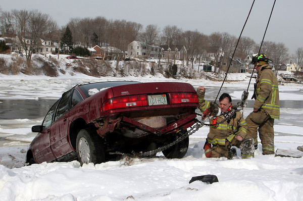 Gloucester: Gloucester firefighters John Nicastro and Phil Harvey, right, assist in getting a car out from behind a snowbank in the Richdale parking lot off Washington Street Saturday monring. The car reportedly lost its brakes and came only a couple feet away from going into the Mill River. Mary Muckenhoupt/Gloucester Daily Times