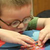 Gloucester: Jonah Backstrom, 3, of Gloucester works on a Valentine's Day card for his dad at the Sawyer Free Library Saturday afternoon.  Children came to the library to make card with Jesse Brown who provided special paper, stickers, ribbons, and stamps to make unique Valentine cards. Mary Muckenhoupt/Gloucester Daily Times