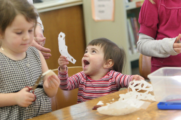Essex: Cadyn Hollingsworth, 21 months, is excited to show her mom Carla the snowflake she made at the TOHP Burnham Library Saturday afternoon.  The library held a Snowflake Festival to celebrate winter and provide fun winter activities including sledding behind the library. Also pictured is Isabella Thurlow, 4. Mary Muckenhoupt/Gloucester Daily Times