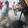 Gloucester: Scott Amero shovels asphalt into a pothole on Eastern Ave as Bill Gilliss, left, and Joe Silva, right, look on yesterday afternoon. The crew repaired a large section of Main Street earlier in the day. Photo by Kate Glass/Gloucester Daily Times Tuesday, February 10, 2009