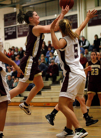 Gloucester's Audrey Knowlton leaps toward the basket as Westport Academy's Suzanne Parker blocks her path during the first round of the Division II North State Tournament at Westford Academy last night. Photo by Kate Glass/Gloucester Daily Times Monday, February 23, 2009