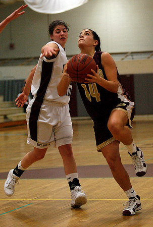 Gloucester's Lindsey Rogers looks toward the net as Westport Academy's Jen Normandie reaches in for the block during the first round of the Division II North State Tournament at Westford Academy last night. Photo by Kate Glass/Gloucester Daily Times Monday, February 23, 2009