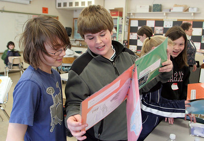Essex: Cole Spencer and Ramsey King read a book on farm animals made by their classmate Campbell Fackre in Joanna Maino's class Thursday afternoon.  The sixth grade students at Essex Elementary School made books to send to kids in refugee camps in Sudan, Afghanistan and China through a program called Kids to Kids International. Mary Muckenhoupt/Gloucester Daily Times