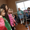 Gloucester: Bailey Saputo bites her nails as she and her classmates from Majestic Preschool sing songs for seniors at the Golden Living Center yesterday. The girls dressed in angel costumes and decorated picture frames for their parents. Photo by Kate Glass/Gloucester Daily Times Monday, February 9, 2009