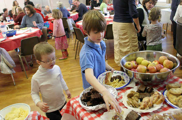 Manchester; Nils Taylor, 6, right, snags a vanilla frosted cupcake as Jonah Backstrom, 3, looks over his options at the Frank Fest at the First Parish Chapel Saturday.  Gourment hot dogs, veggie dogs, salads and side dishes were served as well as the large offering of yummy desserts.  Mary Muckenhoupt/Gloucester Daily Times