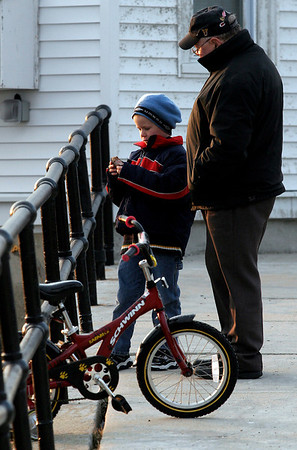 "Gloucester: Andrew Bouchie looks at a shell with his grandfather, Rusty Harnish, while taking a break from riding his bike along Stacy Boulevard on Thursday afternoon. ""I can hardly keep up with him,"" Harnish said, adding, ""I think it's time for the training wheels to come off."" Photo by Kate Glass/Gloucester Daily Times Thursday, February 26, 2009"