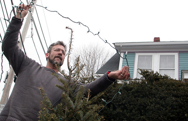 Rockport: Ken Knowles takes down his Christmas lights in front of his house on Upper Main Street Wednesday afternoon.  Knowles was trying to get his lights down before they got covered in snow again. Mary Muckenhoupt/Gloucester Daily Times
