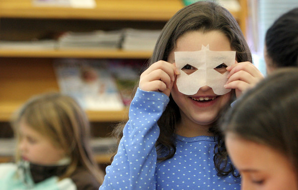 Essex: Rebecca Braimon, 8, of Essex holds up a paper mask a friend made while making snowflakes at the TOHP Burnham Library Saturday. Making one-of-a-kind snowflakes was one of the activities at the library's Snowflake Festival where kids got to also decorate cookies, enjoy hot cocoa and an afternoon of sledding. Mary Muckenhoupt/Gloucester Daily Times