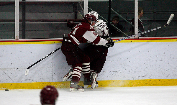 Gloucester's Jared Toye checks Arlington's Joe Stanton into the boards during their game at Arlington last night. Photo by Kate Glass/Gloucester Daily Times Wednesday, February 18, 2009