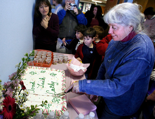 Gloucester: Cathy Talty cuts the cake wishing her good luck as she leaves the Sawyer Free Library after 19 years. Talty was the children's librarian. Photo by Kate Glass/Gloucester Daily Times Saturday, February 21, 2009