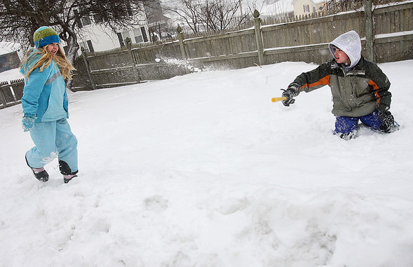 Gloucester: Sierra Rudolf, 9, has a snowball fight with her brother, Josh Rudolf, 12, yesterday afternoon. Josh cut a wiffle ball bat in half and stuffed it with snow to make the snow fly faster. Photo by Kate Glass/Gloucester Daily Times Tuesday, February 3, 2009