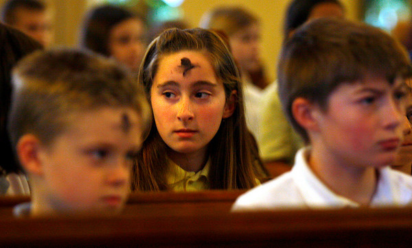 Gloucester: Amanda Mohan, center, looks around St. Ann's Church as Jacob White, left, and Andrew King, right, watch people get ashes during an Ash Wednesday service yesterday afternoon. The children are all fifth graders at St. Ann's School. Photo by Kate Glass/Gloucester Daily Times Wednesday, February 25, 2009