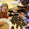 Manchester: Gail Coote holds a pinecone for her son Henry, 3,  the spread shortening on as her daughter Lilly, 5, dips her pinecone in birdseed as they make bird feeders at Manchester Public Library Thursday afternoon. Kids could make birdfeeders with either pinecones, plastic bottles or cardboard orange jiuce containers to help bring birds into the backyard as spring approaches.