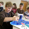 Rockport:  Michael Wanson works on a painting as classmates, including Henry Mattson, right, and his twin brother Preston, look on in Simon Paddock's first and second grade art class Thursday afternoon. The class was working on finishing their pieces for the Rockport Public Schools Annula Art Show. The show will be held at The Rockport Art Association Tuesday, March 3rd through Sunday, March 8th with the opening reception Thursday, March 5th 6:30 to 8. Wonson plans on giving his painting to his mother after the art show. Mary Muckenhoupt/Gloucester Daily Times